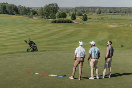 players looking away while standing on golf pitch