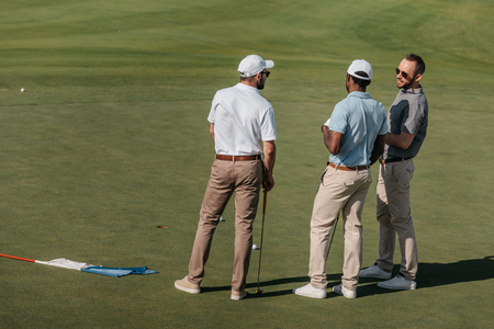 professional golfers talking while standing on green pitch 版權商用圖片 - 83318834