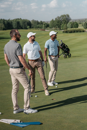 multiethnic golf players looking away while standing on pitch 版權商用圖片 - 83318841