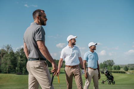 multiethnic golf players looking away while standing on pitch 版權商用圖片 - 83318840