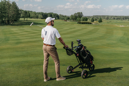 golf player looking away while standing with bag and club on green pitch