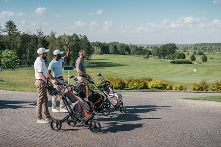 multiethnic friends with sport equipment going to the golf course 版權商用圖片 - 83318849