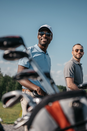 multi-etnische sportmannen gaan naar de golfbaan, tas met clubs op de voorgrond