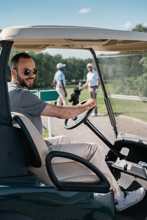 caucasian man in glasses smiling while sitting at golf cart 版權商用圖片 - 83318850