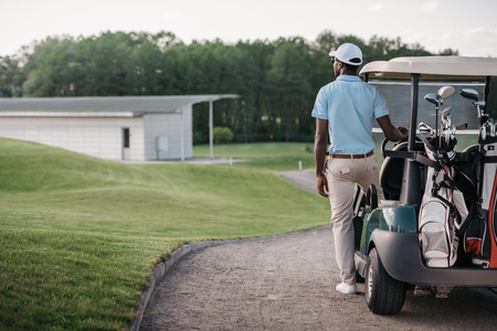golfer looking away while standing near golf cart Stok Fotoğraf