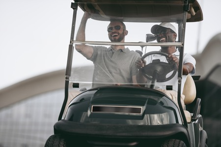multiethnic friends having fun while driving golf cart