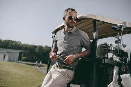 golfer holding golf ball and looking away while leaning on golf cart