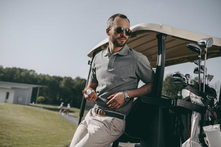 golfspeler golfbal te houden en weg te kijken terwijl leunend op golfkar Stockfoto