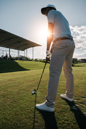 man in cap and sunglasses playing golf with wood and ball Imagens