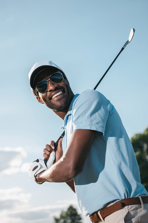 african american man in cap and sunglasses holding club and playing golf