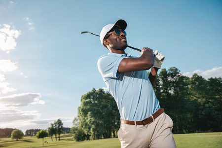 african american man in cap and sunglasses playing golf