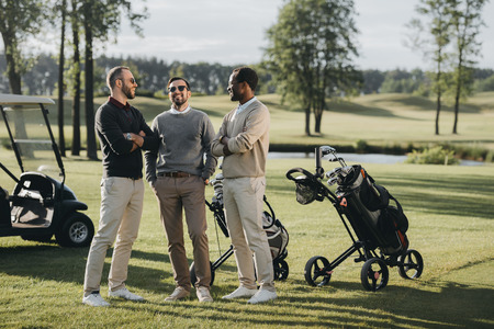 golfers with golf clubs talking and spending time together on golf course Banco de Imagens