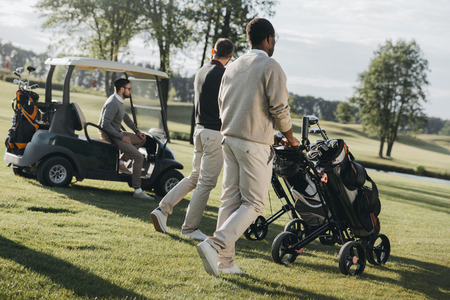 golf players with golf bags and golf cart spending time together Reklamní fotografie
