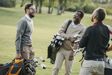 golf players with golf clubs having fun on golf course Standard-Bild