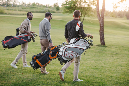 golf players with golf clubs in bags walking on golf course Stockfoto