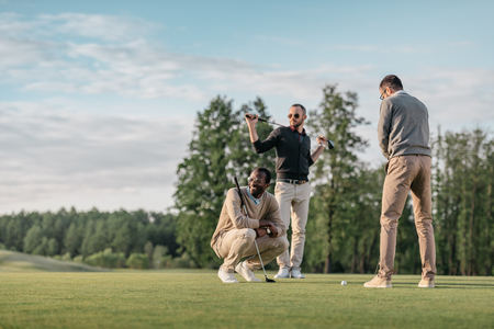 multicultural friends spending time together while playing golf on golf course
