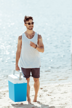 young man in sunglasses holding cooler box while standing on beach