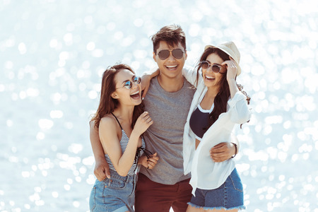 asian man hugging with two cheerful girls on riverside Stok Fotoğraf