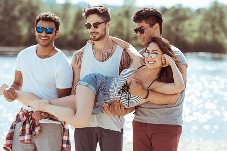 multiethnic men holding attractive asian girl on hands Stok Fotoğraf