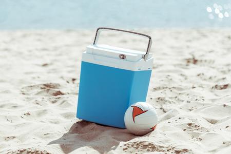 쿨러 상자와 모래 해변에 배구 공