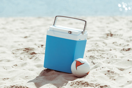 cooler box and volleyball ball on sandy beach