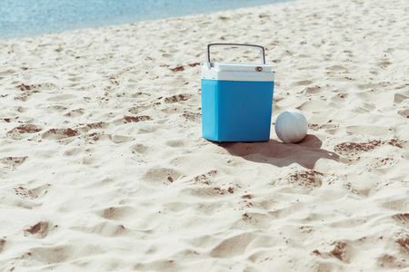 blue cooler box and volleyball ball on sandy beach Banco de Imagens
