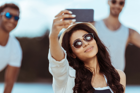 young woman taking selfie with her friends on background
