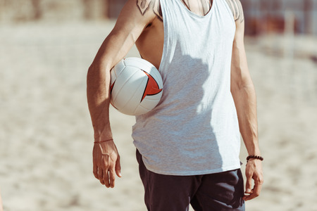 man holding volleyball ball while standing on beach