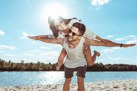 couple piggybacking while spending time on beach on summer day Stock Photo