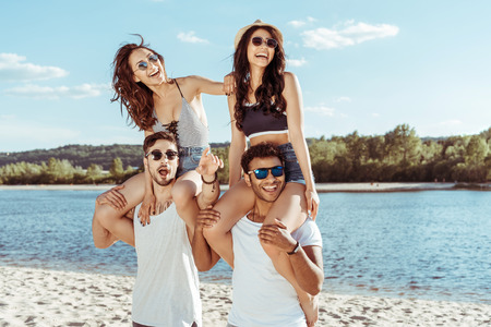 friends piggybacking and looking away while spending time on beach
