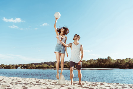 active man and woman playing volleyball on beach together