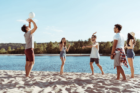multiethnic friends playing volleyball on sandy beach at daytime Stok Fotoğraf