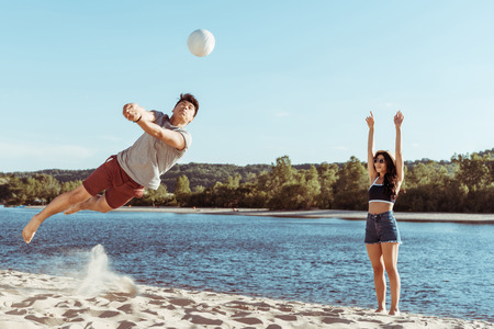 friends playing volleyball on sandy beach at daytime