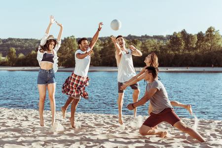 Amis souriants, jouer au beach-volley sur le bord de la rivière pendant la journée Banque d'images - 83460356