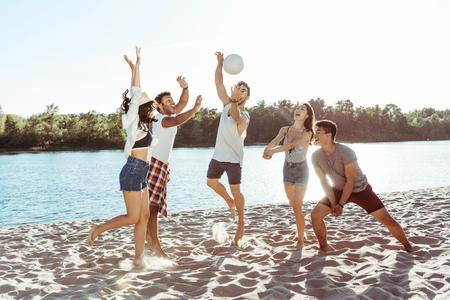 jóvenes amigos jugando voleibol en la playa de arena durante el día Foto de archivo