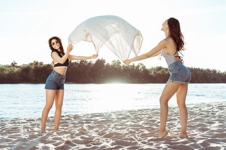 girls waving beach blanket on sandy riverside at daytime Banco de Imagens