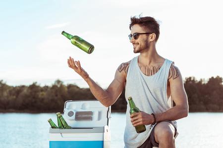 toevallige mens die terwijl jonglerende flessen bier op rivieroever glimlacht