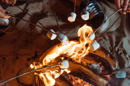 vrienden roosteren zoete marshmallows op vreugdevuur Stockfoto