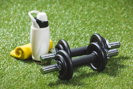 Eisen Hanteln und Flasche Wasser mit Handtuch auf Gras Standard-Bild - 83371308
