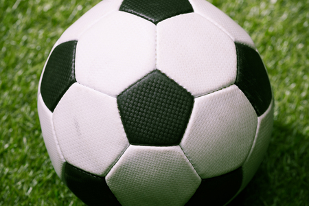 classic soccer ball on green football pitch