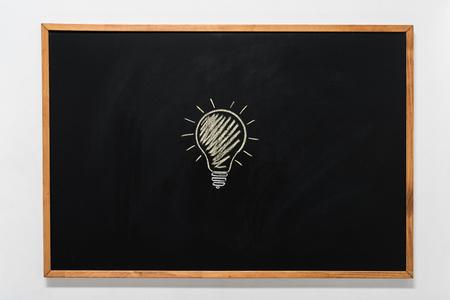 黒い黒板に描かれた電球 写真素材