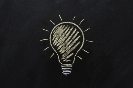 yellow electric bulb drawn on black chalkboard Banco de Imagens - 83374566