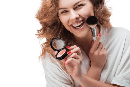Cheerful young woman applying makeup with brush and powder