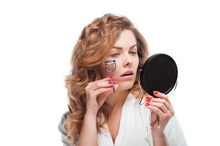 속눈썹을 교정하고 거울을 들고 매력적인 젊은 여성
