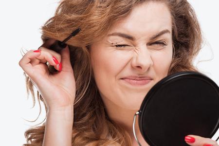 マスカラーを適用する巻き髪の女性の肖像画