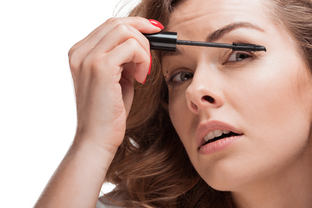 head shot of focused woman applying mascara