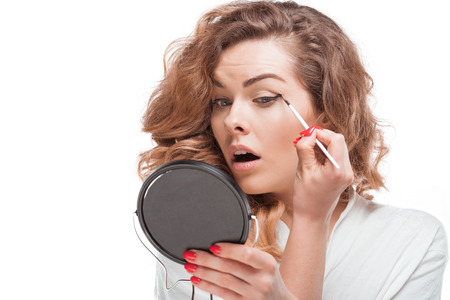 concentrated woman looking at mirror while putting eyeliner