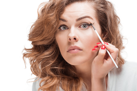focused woman looking at camera while putting eyeliner