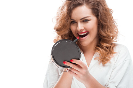 portrait of woman looking at mirror while applying lipstick Stock Photo