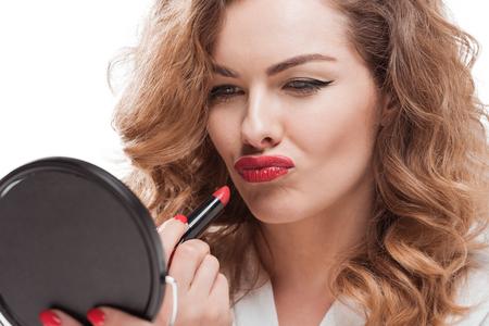 미러를보고있는 동안 립스틱을 손에 적용하는 찌끼 여자